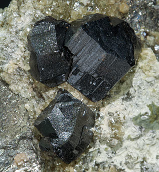 Cassiterite with Arsenopyrite, Fluorapatite, Calcite and Muscovite.