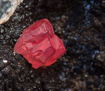 Rhodochrosite with manganese oxides.