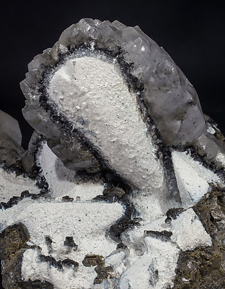 Twinned Calcite with Calcite, Palygorskite and manganese oxides.