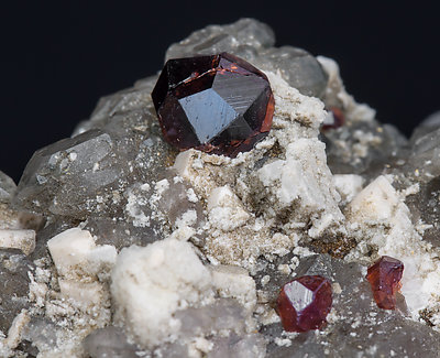 Almandine-Spessartine (Series) with Orthoclase and Quartz (variety smoky).