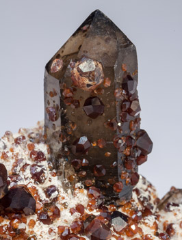 Spessartine with Quartz (variety smoky) and Feldspar.